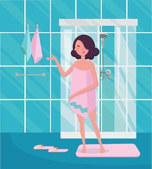 Femme dans une serviette rose debout dans l'intérieur de la salle de bain avec cabine de douche.