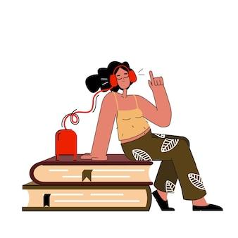 Une femme avec des écouteurs écoute un livre audio ou un livre électronique. concept de podcast. lisant un livre