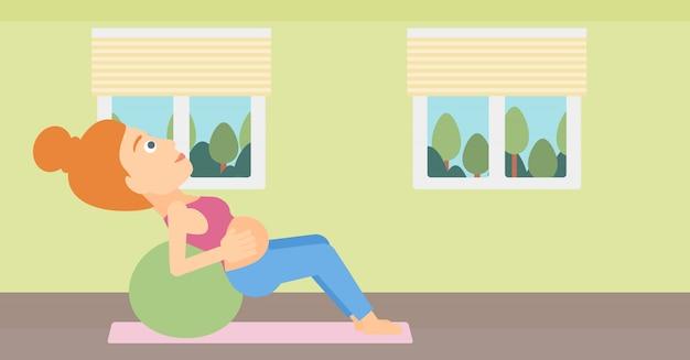 Femme enceinte sur ballon de gymnastique.