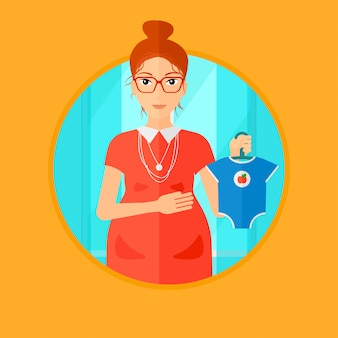 Femme enceinte avec des vêtements pour bébé.