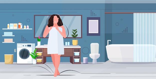 Femme enveloppée de serviette blanche fille brune en surpoids debout après la douche obésité concept de mode de vie malsain salle de bain moderne intérieur plat pleine longueur horizontale