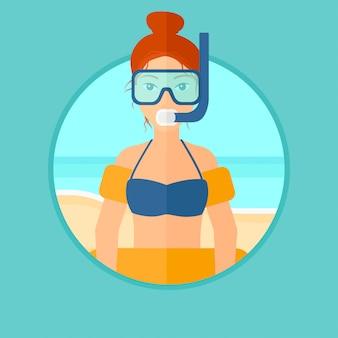 Femme avec des équipements de plongée en apnée sur la plage.