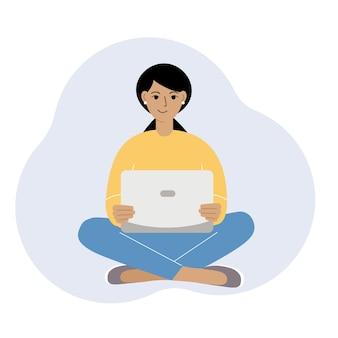 Une femme ou une fille est assise et travaille sur un ordinateur portable. travail à distance ou communication via internet. satisfait, joyeux.