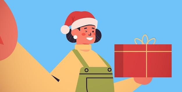 Femme heureuse en bonnet de noel avec boîte-cadeau tenant la caméra et prenant selfie nouvel an vacances de noël célébration concept illustration vectorielle portrait horizontal