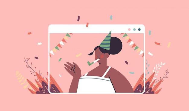 Femme heureuse en chapeau de fête célébrant la fille de fête d'anniversaire en ligne