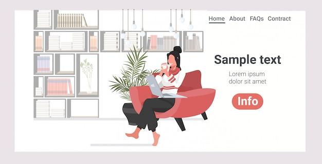 Femme heureuse, séance, à, fauteuil, utilisation, ordinateur portable, landing page