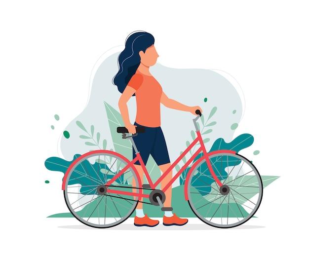 Femme heureuse avec un vélo dans le parc.