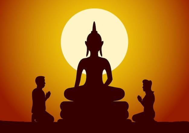 Une femme et un homme bouddhistes respectent la sculpture de bouddha