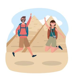 Femme et homme sautant avec sac à dos et appareil photo à l'aventure de la pyramide égyptienne