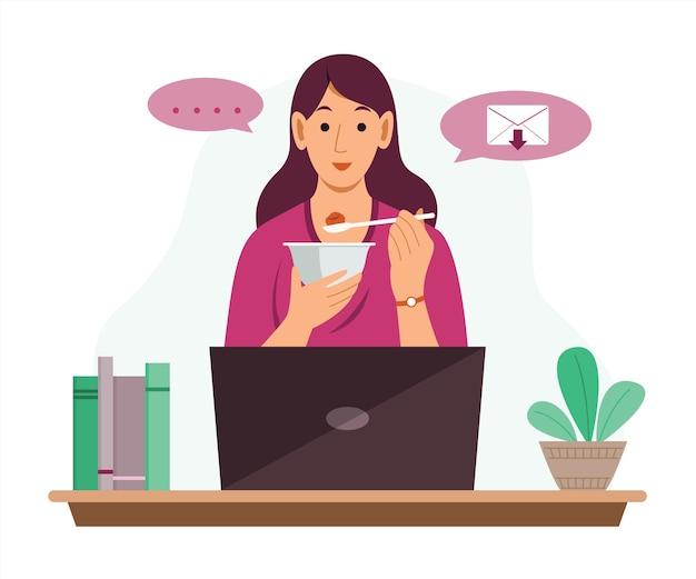 Une femme indépendante travaille en ligne à domicile avec un ordinateur portable et mange de la nourriture