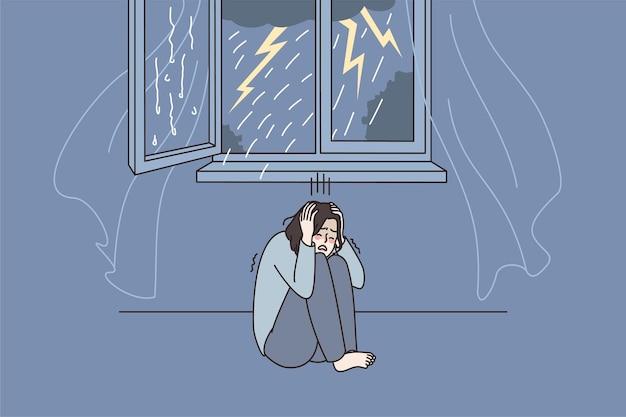 Une femme inquiète a peur de l'orage à la maison