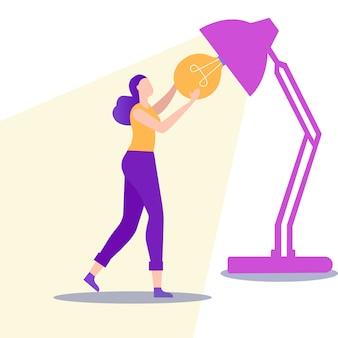 Femme insère une ampoule dans une lampe de bureau. .