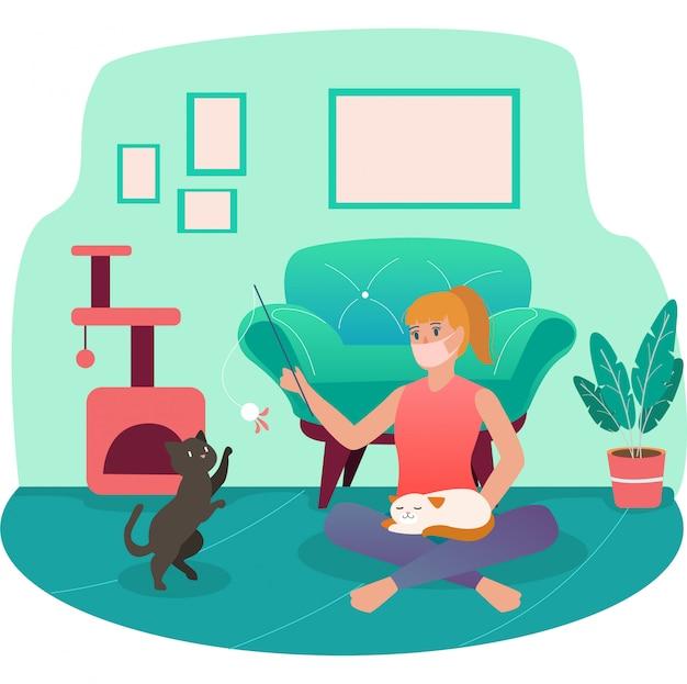 Une femme jouant avec son chat tout en utilisant un masque médical