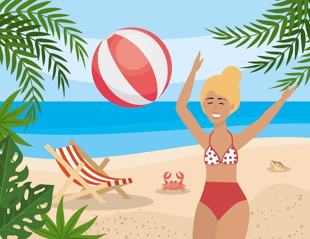 Femme joue avec un ballon de plage et une chaise de bronzage au crabe