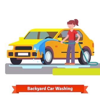 Femme lave sa voiture familiale avec un tuyau de pulvérisation