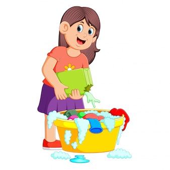 Femme laver les vêtements dans le bassin avec un détergent