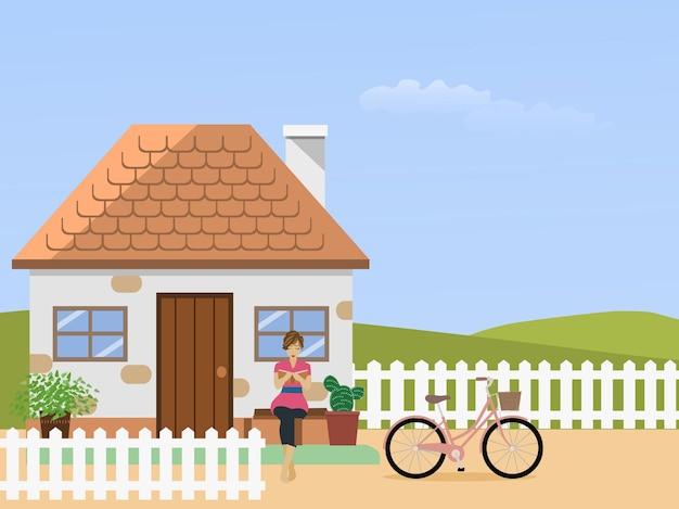Une femme lisant un livre devant une maison blanche. un vélo et une clôture blanche devant avec une colline d'herbe et de ciel en arrière-plan.