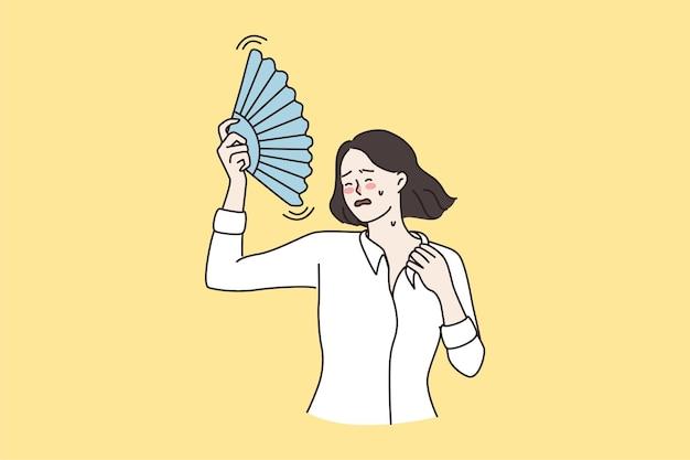 Une femme malade avec un ventilateur à main souffre du temps chaud