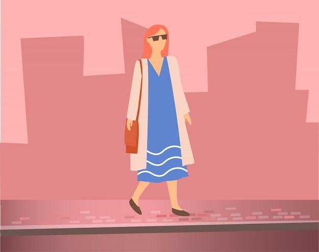 Femme marchant dans la rue, silhouettes d'immeubles