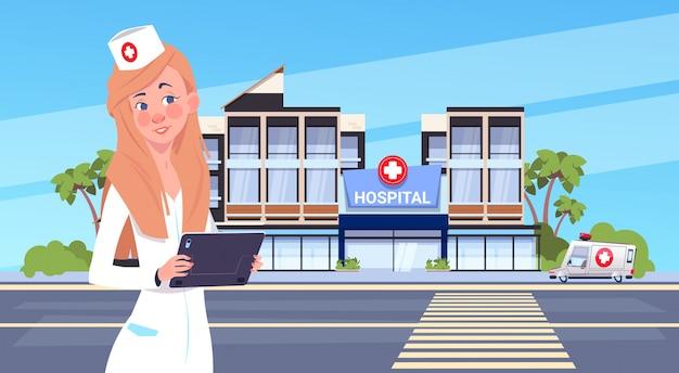 Femme médecin debout sur le bâtiment de l'hôpital moderne