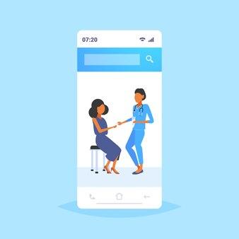 Femme médecin donnant la pilule et le verre d'eau à une femme pharmacien patient offrant des pilules concept de soins de santé écran smartphone application mobile pleine longueur