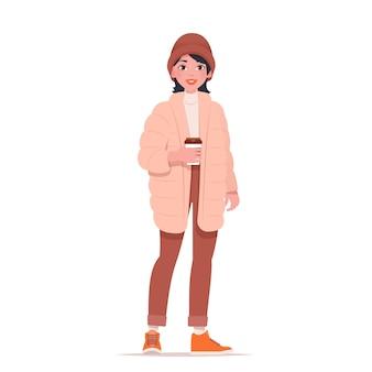 Femme de mode dans des vêtements d'hiver à la mode avec une tasse de café.
