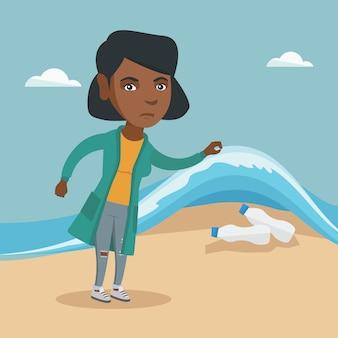 Femme montrant des bouteilles en plastique sous l'eau de mer.