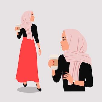 Femme musulmane chic en hijab tenant une tasse de café en papier. appartement