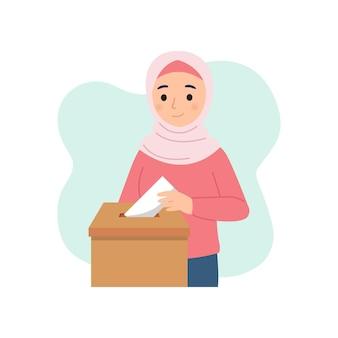 Une femme musulmane insère une enveloppe dans une boîte pour la charité ou le vote