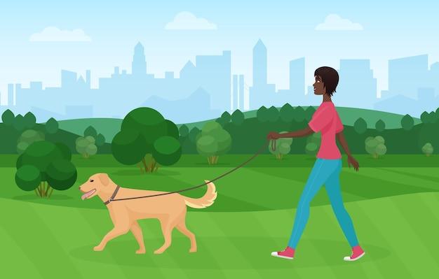 Femme noire afro-américaine marchant avec un animal de compagnie chien golden terrier dans le parc