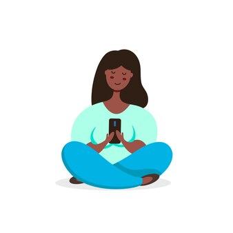 Femme noire méditant en posture de lotus utilise un nouveau smartphone. illustration dans un style plat.