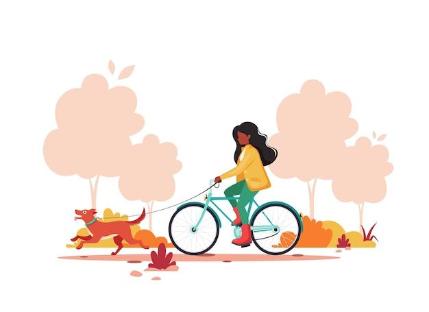 Femme noire à vélo avec chien en automne parc. concept d'activité de plein air.
