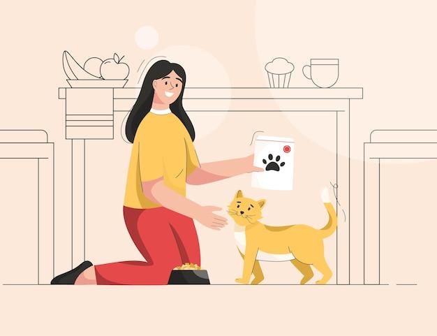 Une femme nourrit un chat chez le propriétaire de la cuisine qui s'occupe d'un chaton