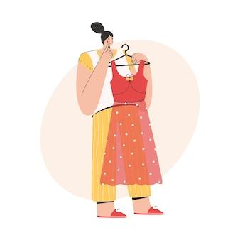 Femme pensant et tenant une robe à la mode sur cintre