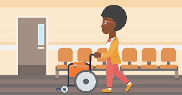 Femme poussant en fauteuil roulant.