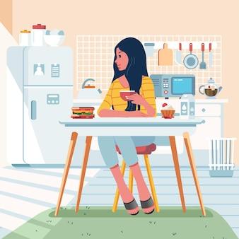 Une femme prend son petit déjeuner à la table à manger dans la cuisine