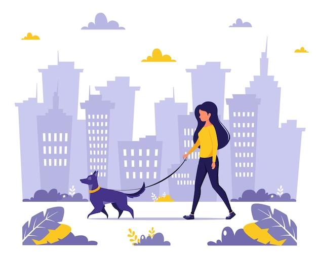 Femme qui marche avec un chien dans la ville