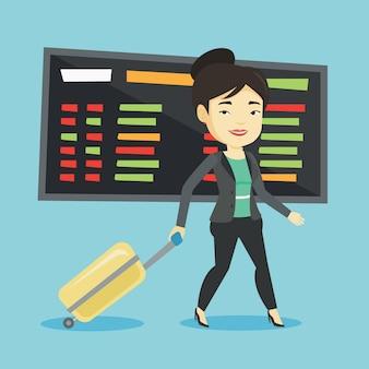 Femme qui marche avec valise à l'aéroport.