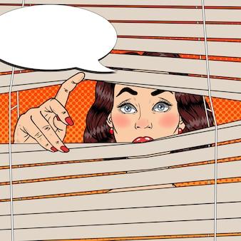 Femme regardant à travers les stores