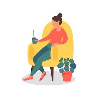 Femme de rêve assise à la maison avec une tasse de thé