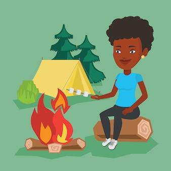 Femme rôtissant guimauve sur feu de camp.