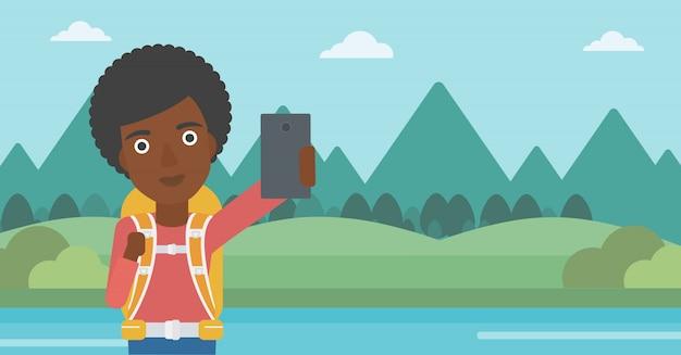 Femme avec sac à dos faisant selfie.