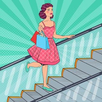 Femme avec des sacs sur l'escalator