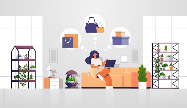 Femme, séance, divan, ordinateur portable, utilisation, informatique, application, achats en ligne, vente, concept, girl, choisir, achats, moderne, salon, intérieur, plat, pleine longueur