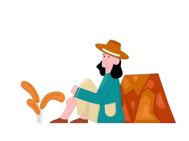 Femme seule assise à côté d'une pierre en automne