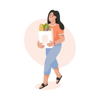 Femme souriante tenant un sac en papier avec des produits alimentaires