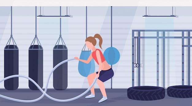 Femme sportive, faire des exercices de crossfit avec une corde de bataille fille s'entraînant dans une salle de sport cardio entraînement moderne boxe combat club studio intérieur concept de mode de vie sain plat pleine longueur horizontal