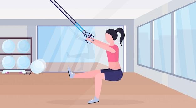 Femme sportive, faire des exercices avec suspension sangles de fitness corde élastique fille formation crossfit concept d'entraînement moderne gym studio intérieur horizontal plat pleine longueur