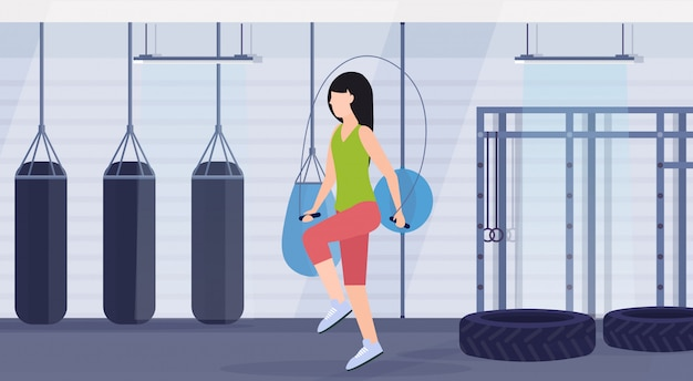 Femme sportive faisant des exercices avec corde à sauter fille formation entraînement crossfit concept de mode de vie sain plat club de combat moderne avec des sacs de boxe intérieur horizontal de gym