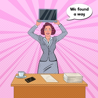 Femme tenant un ordinateur portable devant la table